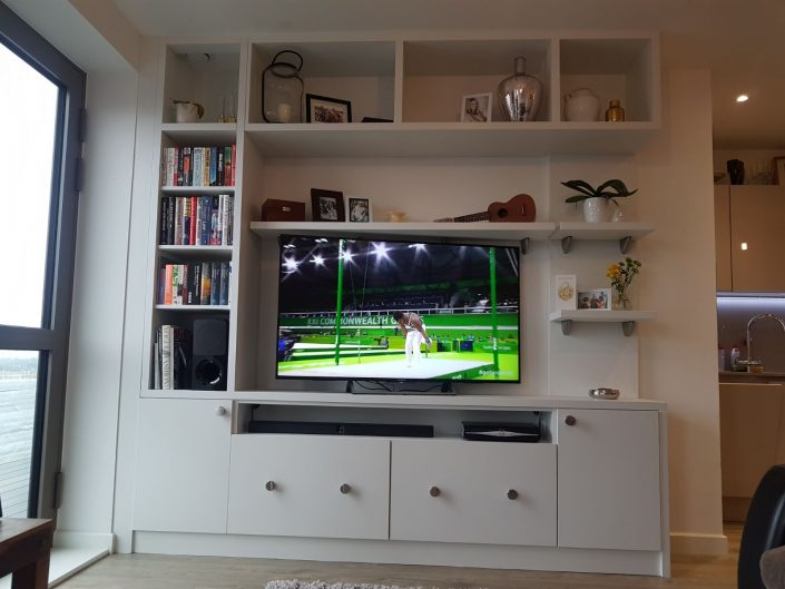 television white fitted unit and book rack.